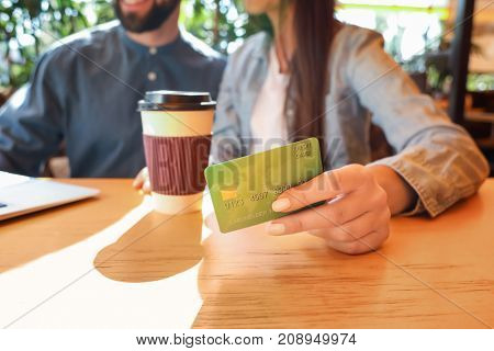 Couple with credit card in cafe