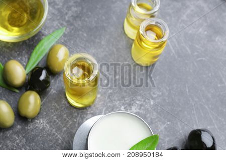 Composition with olive oil and cosmetics on grey table