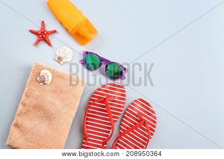 Composition with towel and summer accessories on light background