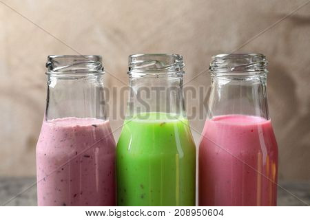 Bottles with different protein shakes on table, closeup