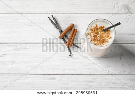 Vanilla and cinnamon protein shake in glass on table