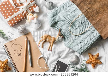 Christmas planning and shopping background. Blue knitted sweater in a paper bag notepad phone christmas decoration on a light background top view. Christmas still life