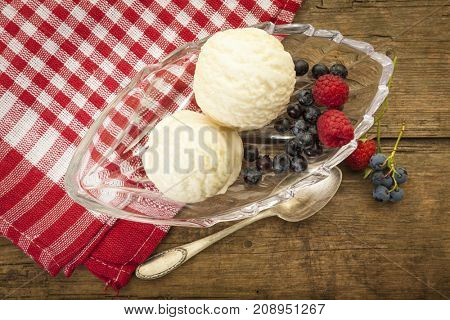 vanilla ice cream in glass bowl with raspberries and blueberries, birds view