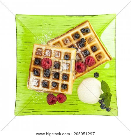 Belgian waffles with ice cream, raspberries and blueberries on green glass plate isolated on white background, birds eye view