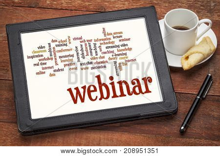 webinar (web seminar) and online education word cloud on a  digital tablet with cup of coffee