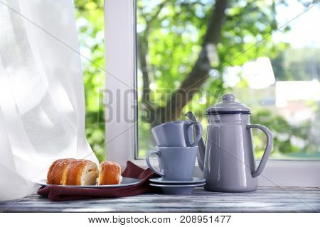 Composition of teapot and cups with baked roll on windowsill
