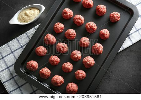 Baking tray with raw meatballs on table