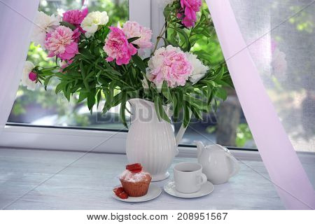 Delicious muffin and vase with beautiful peony flowers on windowsill