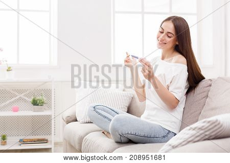 Happy girl sitting on a couch at home looking at the results of her recent pregnancy test. Family, child expectation and maternity concept