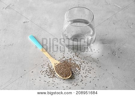 Spoon with chia seeds and glass of water on table