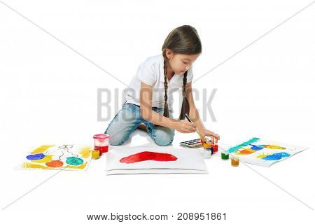 Little cute girl painting picture against white background