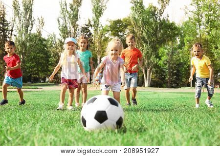 Cute children playing with ball on lawn