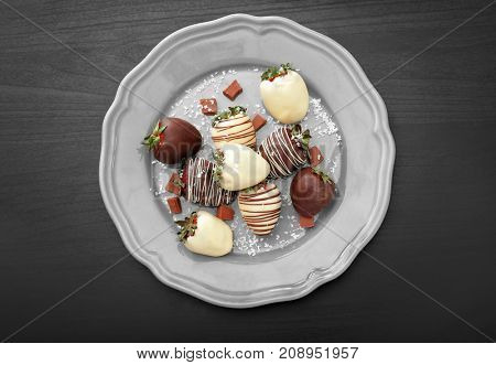 Plate with tasty glazed and chocolate dipped strawberries on table