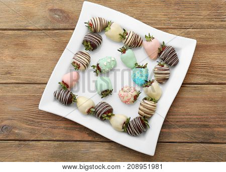 Plate with tasty chocolate dipped strawberries on table