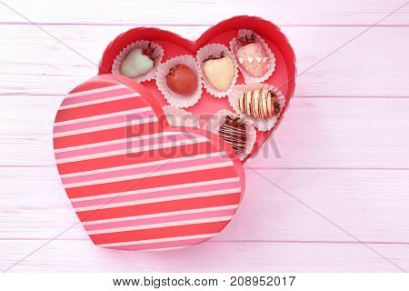Heart-shaped box with tasty glazed and chocolate dipped strawberries on wooden table