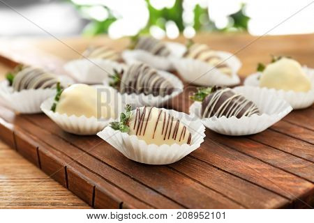 Tasty chocolate dipped strawberries on wooden board, closeup