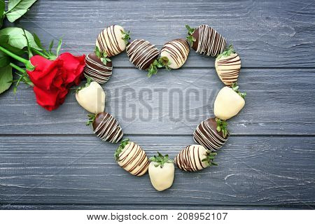 Heart made of tasty chocolate dipped strawberries on wooden table