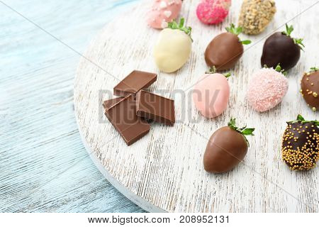 Tasty chocolate dipped and glazed strawberries on wooden board