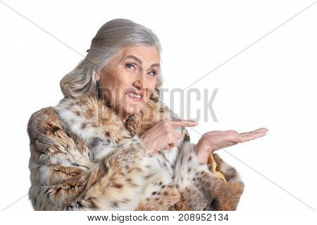 Senior woman in fur point the finger on something on white background