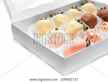 Box with tasty chocolate dipped and glazed strawberries on white  background, closeup