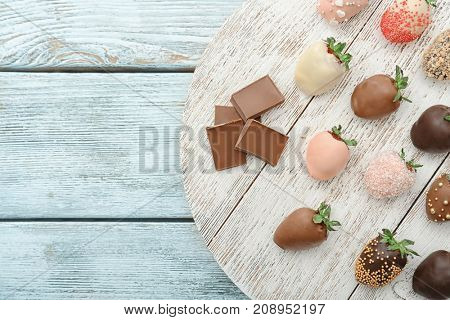 Tasty chocolate dipped and glazed strawberries on wooden table
