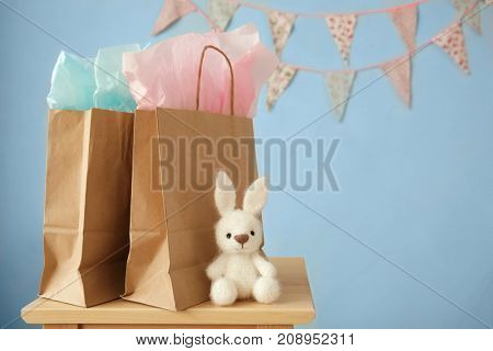 Shopping bags and toy rabbit on stool