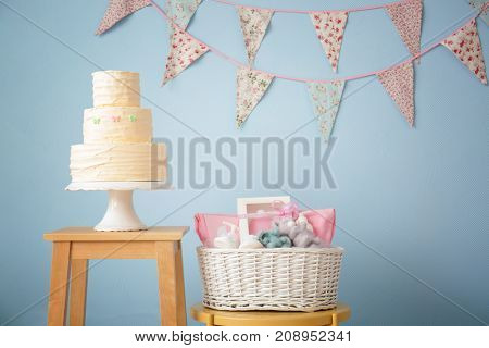 Basket with baby shower gifts and tasty cake on stools indoors