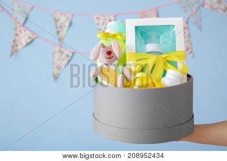 Woman holding cardboard box with baby shower gifts indoors