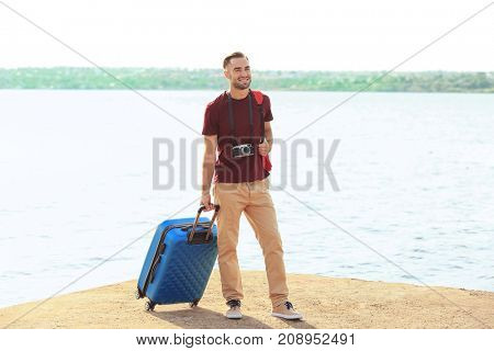 Handsome young tourist with suitcase standing on river bank