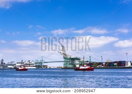 Two red tugboat motors across ports of call in Long Beach California in route to escort a freighter to the loading docks.