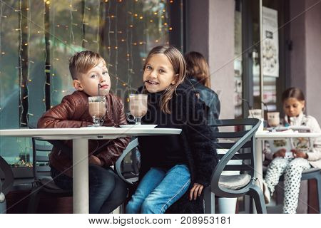 Children having fun in outdoor cafe. Kids talking and eating dessert in the city street. Autumn weekend with friends.