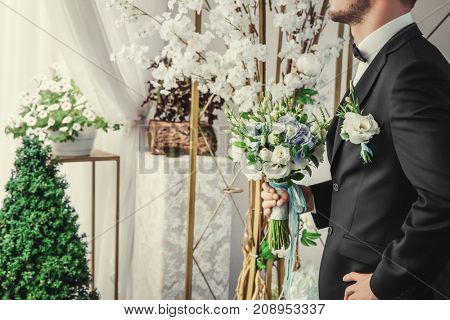 Groom holding bouquet in wedding hall