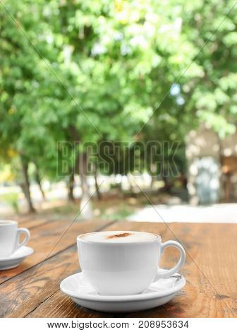 Cup of delicious coffee on wooden table outdoors