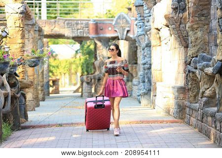 Beautiful young tourist with suitcase near ancient castle