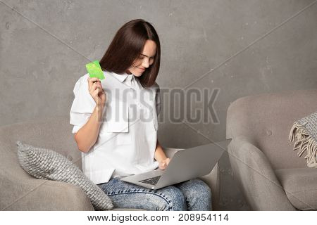 Young woman using laptop while holding credit card on grey background. Internet shopping concept