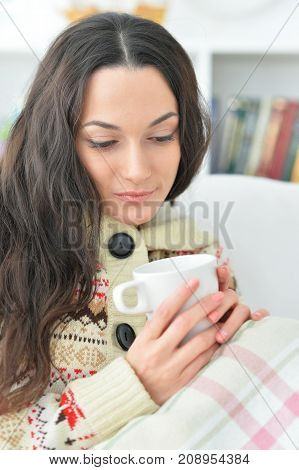 young beautiful woman with a cup of tea on sofa at home