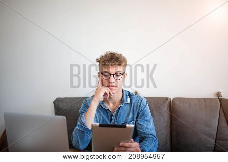 Serious man IT support specialist reading information in network via touch pad, siting in office near wall with copy space. Young male magazine editor working in internet via portable digital tablet