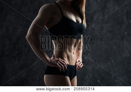 Sports sexy girl with big muscle belly in a black sportswear on a black background. A six-pack on his stomach in black color. Taut, pumped up, firm abdomen.