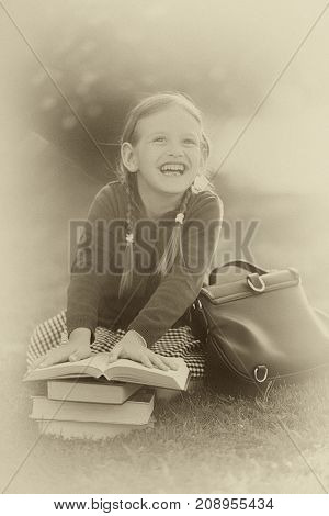 Old-fashioned little girl wearing school uniform. Smiling holding pile of schoolbooks laughing reading. back to school concept. Horizontal old vintage retro monochrome black and white photo.