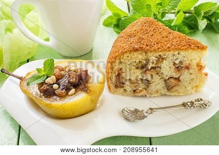 Sweet dessert: baked pear with raisins dates honey nuts spices and slice of delicious pie with apples on white plate mug with tea and mint on green wooden table with yellow gauze napkin