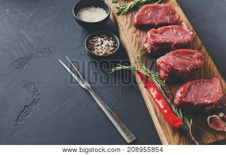Raw filet mignon steaks with herbs and spices. Cooking ingredients for restaurant dish. Fresh meat, salt, rosemary, garlic and chilli on wooden board, meat fork at black background with copy space