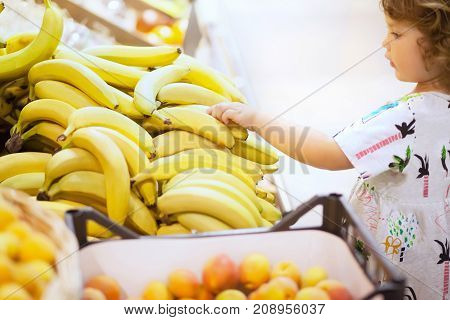 Little girl at supermarket Healthy lifestyle for young family with kids.