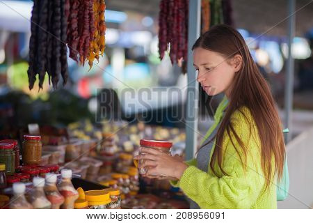 Young woman at the bazaar buying food ingridients.