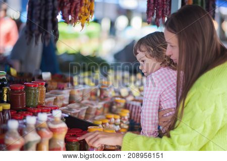 Young woman and her daughter at the bazaar buying food ingridients.