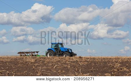 a large blue tractor plowing field against the beautiful sky. Work of agricultural machinery. Harvest