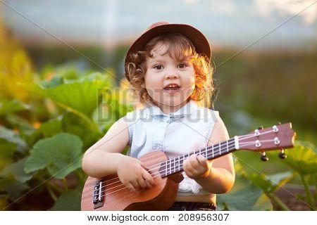 Music education little musician art school. Toddler girl play ukulele guitar.