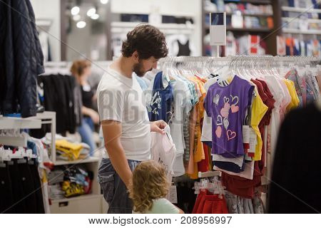 Attractive young man and his cute little daughter at the kids apparel shop bying clothes together.