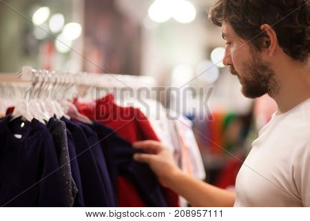 Attractive young father at the kids apparel shop bying clothes for his child.