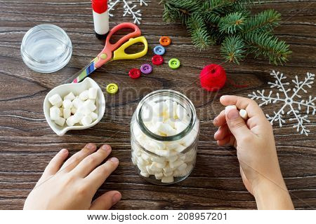 A Child Is Folding A Jar Of Marshmallow Details Of A Christmas Present With A Snowman Sweets. Made B