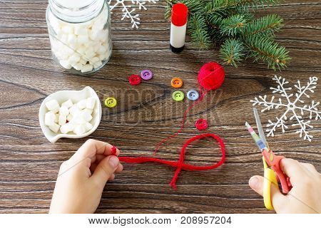 The Child Cuts The Details Of A Christmas Gift With A Snowman Sweets. Made By Own Hands. Children's